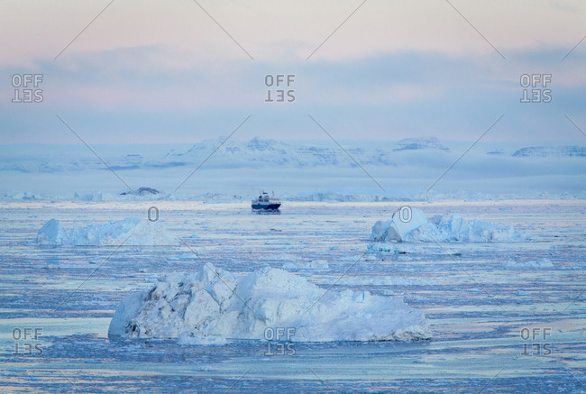 Boat on ocean at sunset with icebergs in background, Greenland