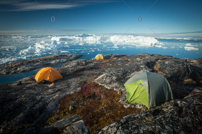 Tent on rocky shore overlooking icefjord and icebergs