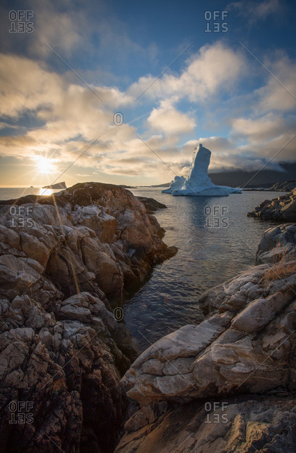 Towering iceberg off rocky shore of Ilulissat, Greenland