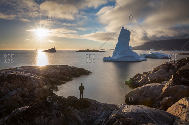 Person on rocky shore overlooking towering iceberg