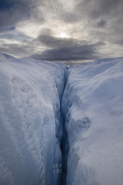 Blue ice crevasses on snowy glacier