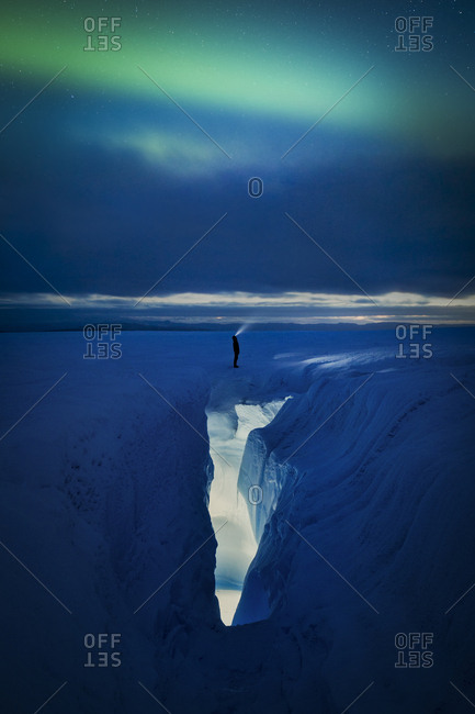Person standing above an ice crevasse looking at the Aurora Borealis