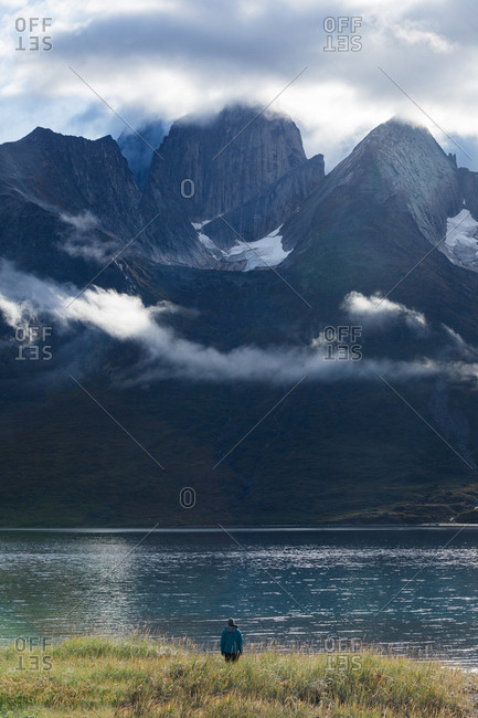 Person walking along lake amongst jagged mountain peaks and clouds