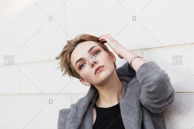 woman in gray coat adjusts her stylish short hairstyle