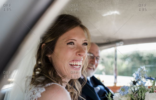 a bride laughing in her car on her wedding day