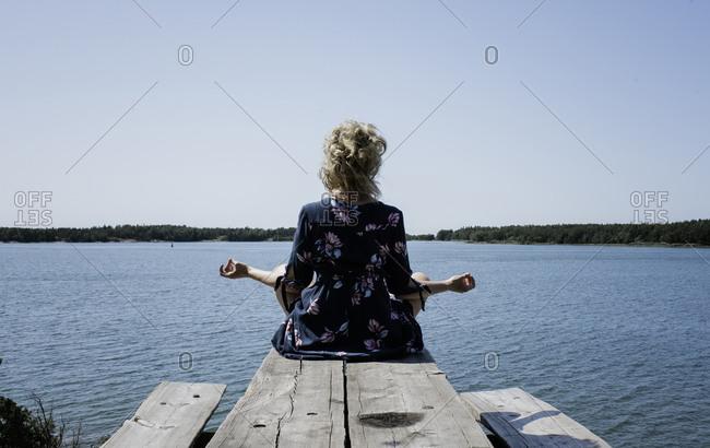 Woman sat meditating outside looking at the sea on holiday