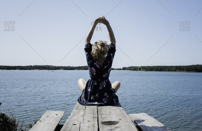 woman stretching whilst meditating in front of the sea