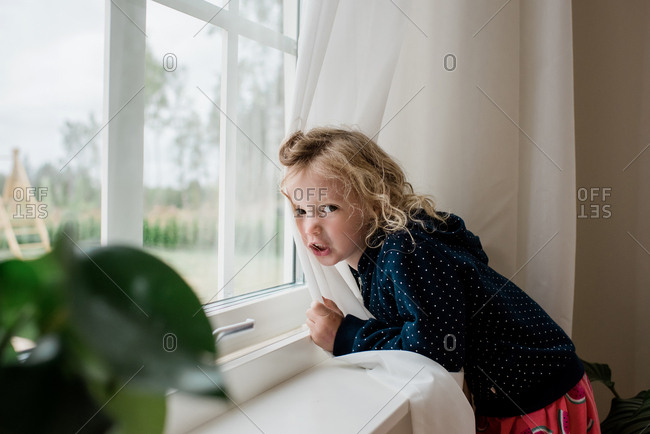 Portrait of a girl leaning against a window scowling