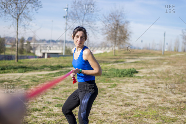 Female athlete exercising with resistance band on grassy field