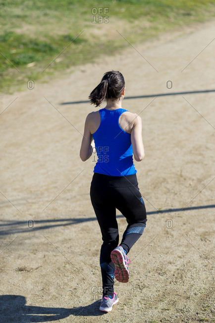 Woman with ponytail running in a park in a sunny day