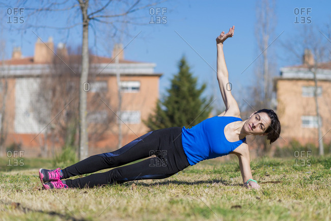 Woman with ponytail stretching on a park grass on sunny day