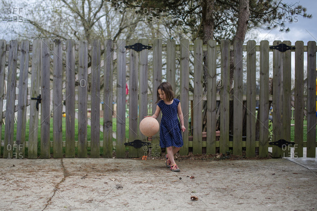 a small girl dribbles a basketball in a driveway in front of fence