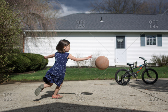 A small girl chases a basketball in driveway against cloudy sky