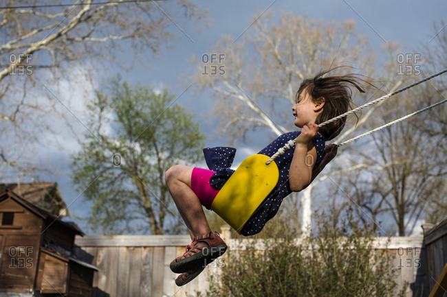 A happy girl on a yellow swing on a breezy, stormy spring day