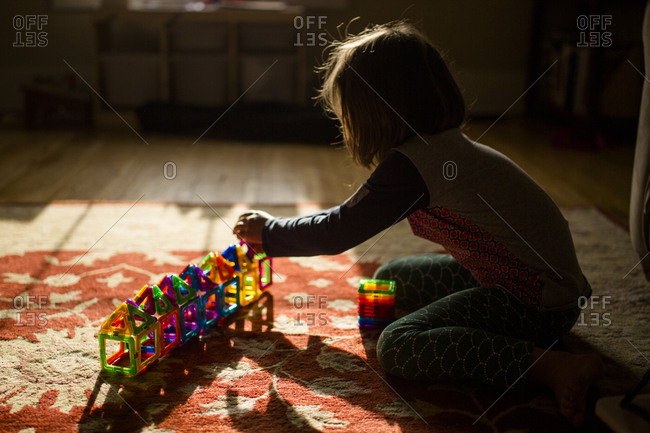 A child sits on the floor in golden morning light building with tiles