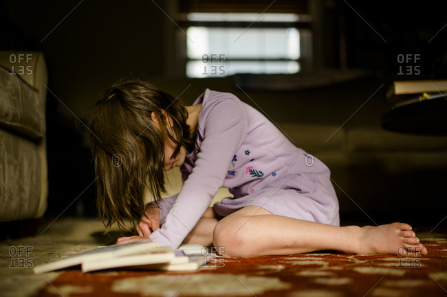 A small child sits on rug in morning light with pile of books reading