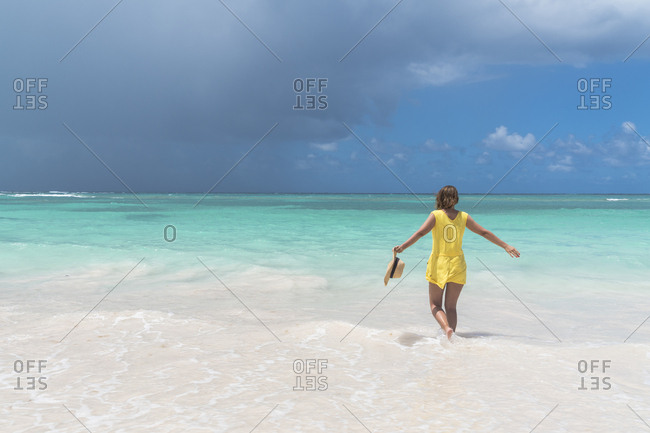 Rear view of cheerful woman in the crystal Caribbean Sea