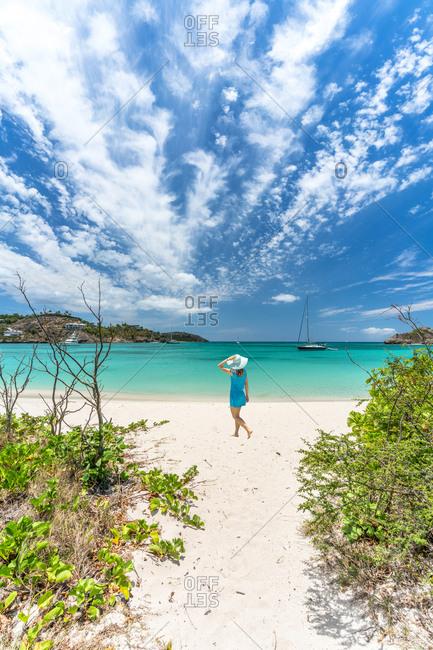 Rear view of woman walking on tropical beach, Caribbean Sea, Antilles