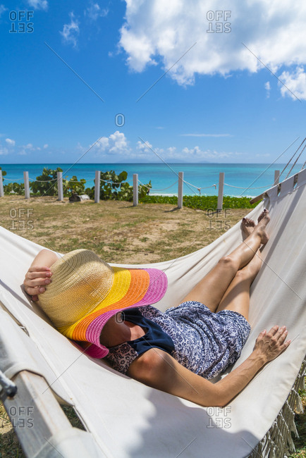Woman with sun hat resting on hammock in a tropical garden, Caribbean