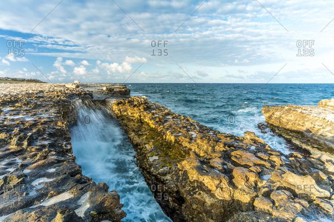 Waves crashing on limestone cliffs, Devil's Bridge, Antigua, Caribbean