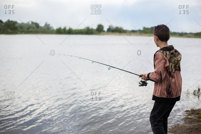 Boy fishing in pond by himself