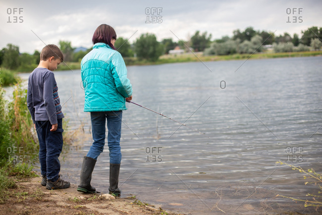 Siblings fishing in pond looking at water