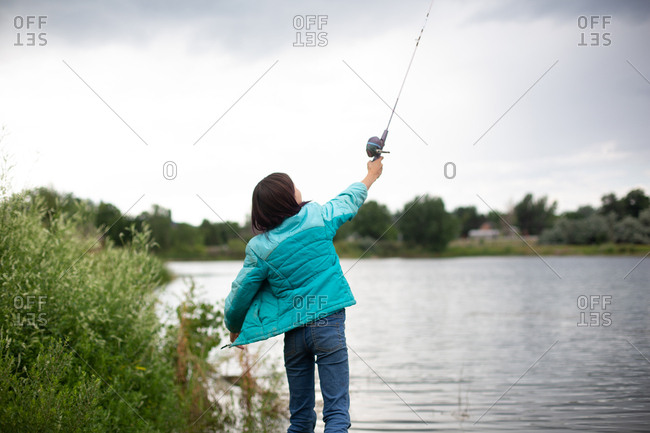 Girl casting fishing line over her head