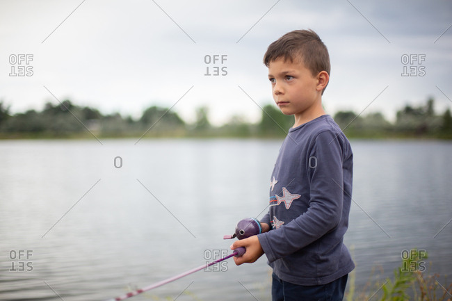 Little boy holding fishing pole at the side of a pond