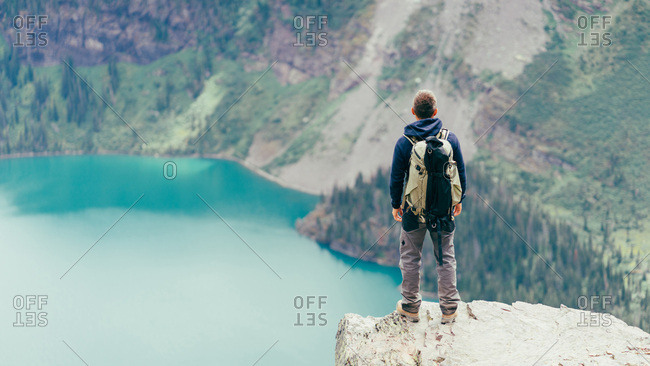 Male hiker is standing on a cliff looking at the lake in Glacier NP