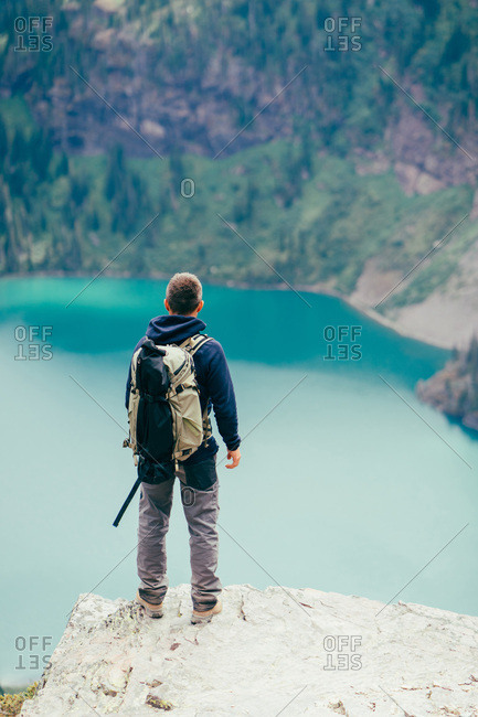 Hiker is standing on a cliff looking at the lake in Glacier National Park, Montana