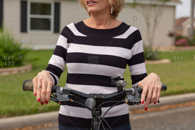 Mature woman in her seventies enjoying a day outside on her bike.