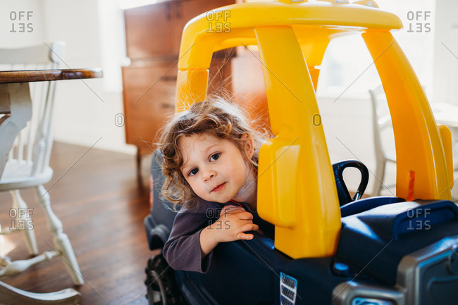 Young girl looking at camera sitting in toy car inside dining room