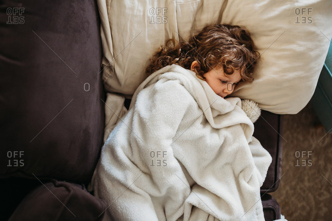 Young girl laying on couch while sick
