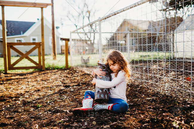 Young girl sitting outside hugging toy own in spring