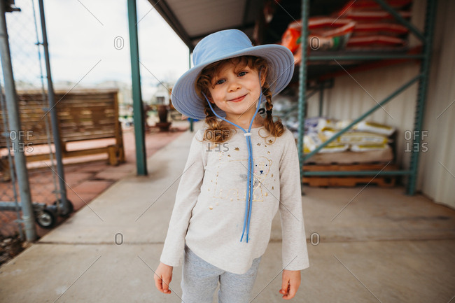 Young girl smiling wearing sun hat outside of garden center