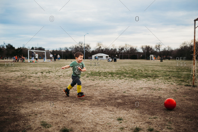 Young boy running towards soccer ball outside