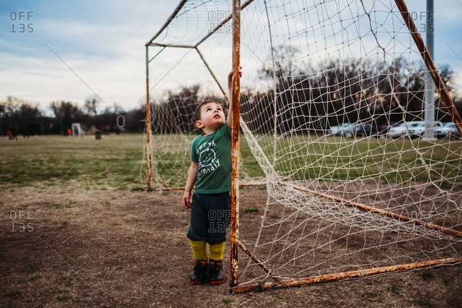 Young boy standing inside soccer goal wearing cleats