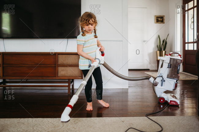 Young girl helping vacuum rug in living room