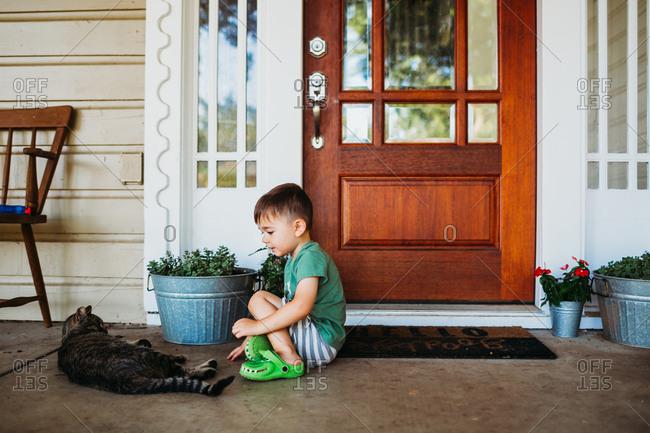 Young boy sitting outside front door petting short hair cat