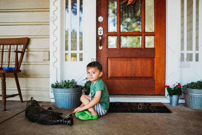 Young boy sitting outside front door with pet cat
