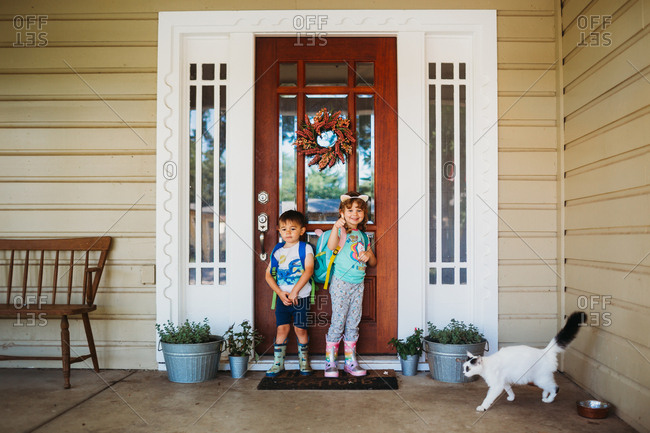 Young boy and girl standing outside front door wearing back packs