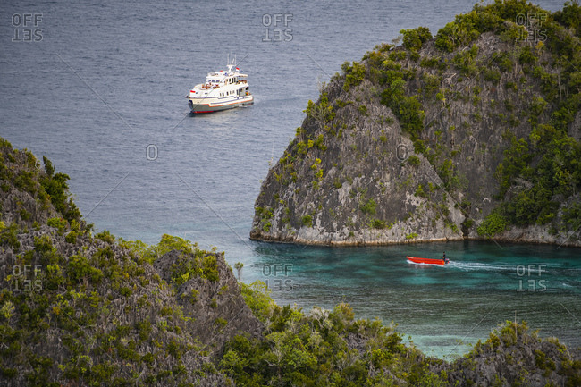 small boat heading out to sea at the archipelago of Raja Amapat