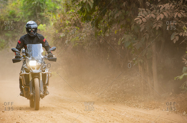 Man riding his ADV motorbike on rural dirt road in Cambodia