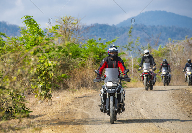 group of men riding their ADV motorbikes on gravel road in Cambodia
