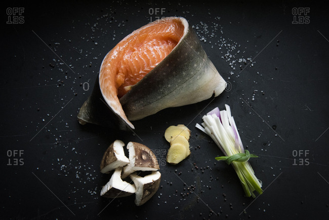 Raw salmon fillet with mushrooms, ginger, onion and salt on black tile