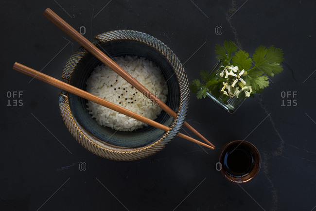 An Asian-style bowl of rice with chopsticks, soy sauce, herb on black