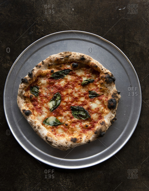 Artisan pizza on grey metallic plate against brown background