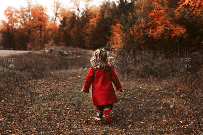 Child walking outside wearing red coat on a beautiful fall day