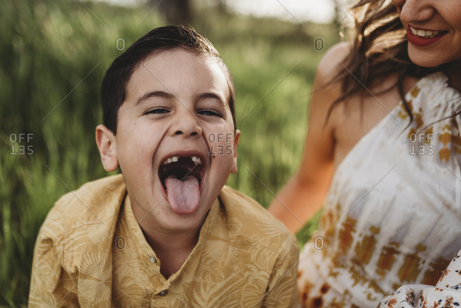 Close up portrait of young boy sticking his tongue out