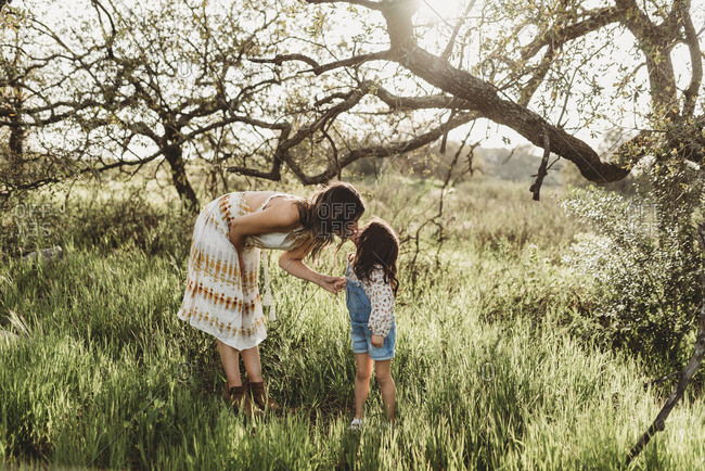 Side view of mother bending down to kiss daughter in backlit field